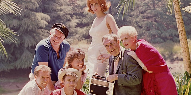 """The """"Gilligan's Island"""" cast, from left, Russell Johnson (as the Professor, in white shirt), Alan Hale Jr. (as the Skipper, in blue shirt), Bob Denver (as Gilligan, in red shirt), Dawn Wells (as Mary Ann, hand on chin), Tina Louise (as Ginger, standing), Jim Backus (as Thurston Howell III, holding radio), and Natalie Schafer (as Mrs. Howell)."""