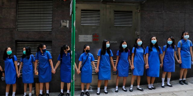 Students wearing mask hold hands to surround St. Stephen's Girls' College in Hong Kong, Monday, Sept. 9, 2019. (AP Photo/Kin Cheung)
