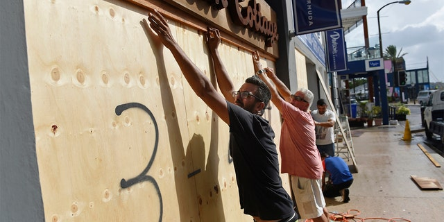People board up an Urban Cottage store in preparation for Hurricane Humberto in Hamilton, Bermuda, Wednesday, Sept. 18, 2019.