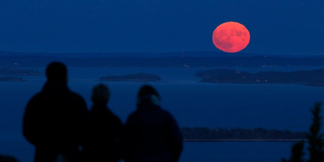 Jack and Kathy Duepree, of Camden, Maine, left and center, and their friend Betsy Starman, of Naples, Fla., watch the nearly-full harvest moon rise over Penobscot Bay, Friday.