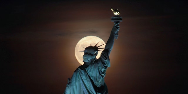 The Friday the 13th harvest moon rises behind the Statue of Liberty.