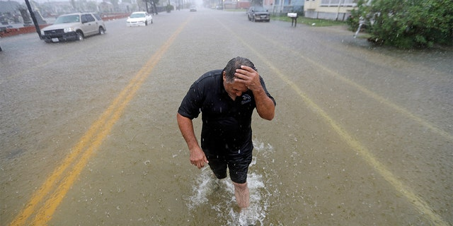 Angel Marshman wades through floodwaters from Tropical Depression Imelda after trying to start his flooded car Wednesday, Sept. 18, 2019, in Galveston, Texas.