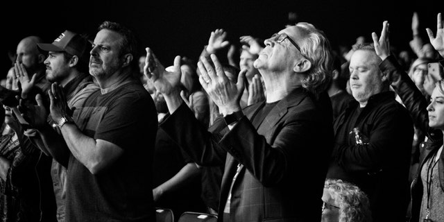 "Kris Vallotton, senior associate leader of Bethel Church and co-founder of the Bethel School of Supernatural Ministry, pictured left, claps during worship as lead senior pastor, Bill Johnson, worships with his hands out, during Bethel Music's ""Heaven Come"" conference in Los Angeles, Calif., earlier this year."