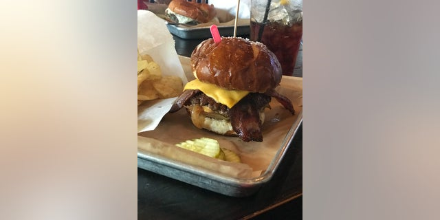 "The ""Labor Inducer"" burger contains an angus beef patty, honey-cured bacon, peach caramelized onions, spicy mustard and Cajun remoulade on a pretzel bun."