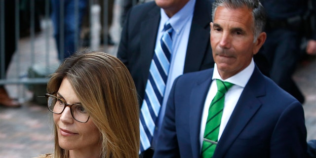 Actress Lori Loughlin, left, leaves as her husband Mossimo Giannulli, right, trails behind her outside of the John Joseph Moakley United States Courthouse in Boston on April 3, 2019.