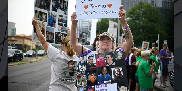 In this Aug. 17, 2018, file photo, Lynn Wencus of Wrentham, Mass., holds a sign with a picture of her son Jeff and wears a sign of others' loved ones lost to OxyContin and other opioids during a protest at Purdue Pharma LLP headquarters in Stamford, Conn. (AP Photo/Jessica Hill, File)