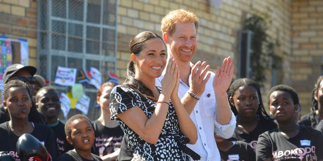 Prince Harry and Meghan Duchess of Sussex, greet youths on a visit to the Nyanga Methodist Church on Sept. 23, 2019, in Cape Town, South Africa.