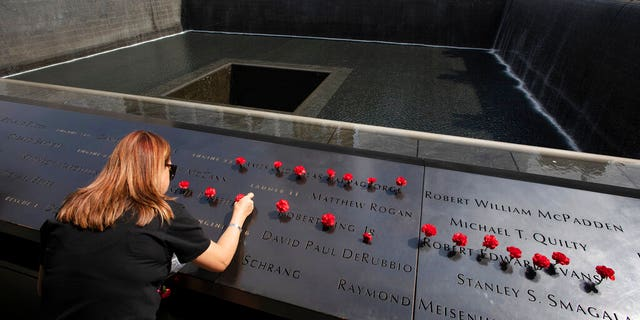 Norma Molina, of San Antonio, Texas, leaves flowers by the names of firefighters from Engine 33 at the September 11 Memorial, Monday, Sept. 9, 2019, in New York. Her boyfriend Robert Edward Evans, a member of Engine 33, was killed in the north tower of the World Trade Center on Sept. 11, 2001. (AP Photo/Mark Lennihan)