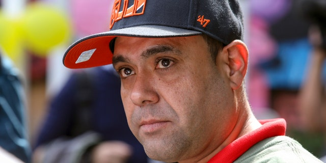 Miguel Perez Jr. listens to a supporter speaking at a news conference in Chicago on Tuesday. (AP Photo/Teresa Crawford)