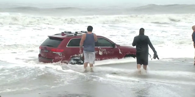 People can be seen taking pictures of the stuck Jeep before being cleared out of the area by police.