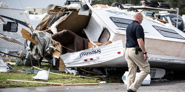 Bill Bailey, assistant chief of the Emerald Isle Police Department, walks past a damaged trailer in the Holiday Trav-l Park on Thursday, Sept. 5, 2019, in Emerald Isle, N.C, after a possible tornado generated by Hurricane Dorian struck the area.