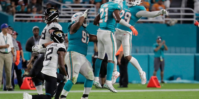 Miami Dolphins cornerback Eric Rowe (21), safety Minkah Fitzpatrick (29) and defensive tackle Christian Wilkins (97) celebrate an interception during the first half of an NFL football preseason game against the Jacksonville Jaguars on Aug. 22, 2019, in Miami Gardens, Fla. (AP Photo/Lynne Sladky)