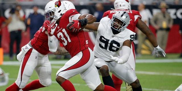 Former Arizona Cardinals running back David Johnson (31) runs as Oakland Raiders defensive end Clelin Ferrell (96) defends during the first half of an NFL preseason football game in Glendale, Ariz. (AP Photo/Rick Scuteri, File)