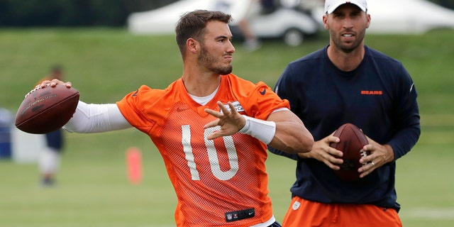 Chicago Bears quarterback Mitchell Trubisky throws a ball as quarterbacks coach Dave Ragone looks on during an NFL football training camp on July 26, 2019, in Bourbonnais, Ill. (AP Photo/Nam Y. Huh, File)