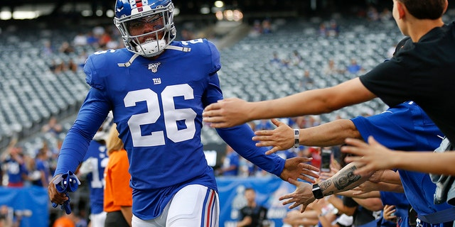 FILE - In this Aug. 16, 2019, file photo, New York Giants running back Saquon Barkley (26) greets fans before an NFL football game against the Chicago Bears in East Rutherford, N.J. (AP Photo/Adam Hunger, File)