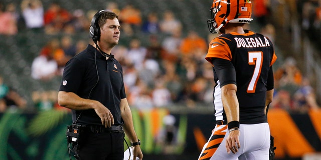 Cincinnati Bengals coach Zac Taylor, left, meets with quarterback Jake Dolegala (7) during the second half of the team's NFL preseason football game against the Indianapolis Colts, Thursday, Aug. 29, 2019, in Cincinnati. (AP Photo/Frank Victores)