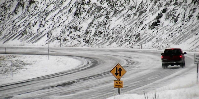 A motorist travels along U.S. 287 near Norris, Mont. during a snowstorm on Sunday.