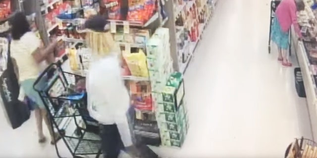 The video of the theft shows the thief slowly sneaking her hand into the woman's purse as she had her back turned and grabbing what appears to be a wallet as her alleged accomplice looked on. The two then walked off.