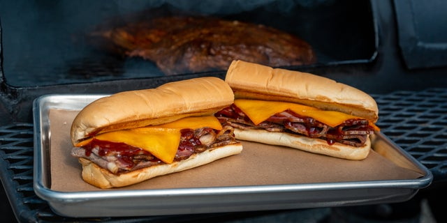 The pit-smoked brisket sandwich is stacked with brisket that is slow-smoked for at least 13-hours before being topped with smoked cheese and barbecue sauce.