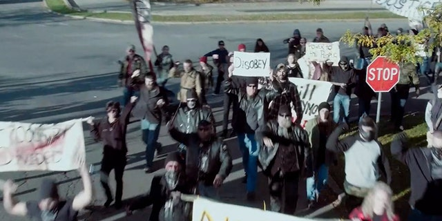 """A still from the upcoming movie """"The Reliant"""" featuring protesters rioting in a small U.S. town."""