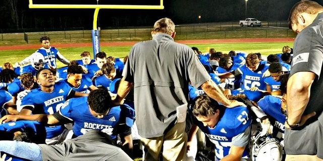 Rockvale High School Football Coach Rick Rice leads a team prayer, a practice that came under fire from the Freedom From Religion Foundation.