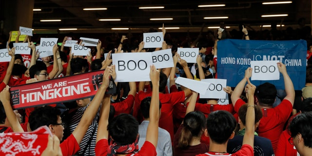"Hong Kong soccer fans turn their back and boo the Chinese national anthem as they chant ""Hong Kong is not China"" during the FIFA World Cup Qatar 2022 and AFC Asian Cup 2023 Preliminary Joint Qualification Round 2 soccer match between Hong Kong and Iran. (AP Photo/Kin Cheung)"
