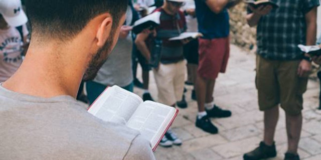 Students read their Bibles at a holy site in Israel with the Passages Israel trip.