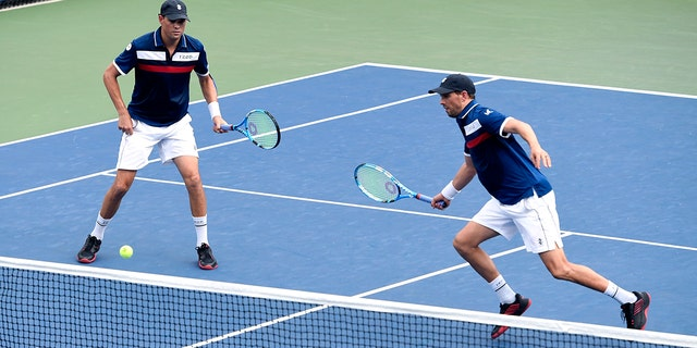 Mike Bryan, left, returns a shot as his brother Bob Bryan, looks on during a first round doubles match against Hubert Hurkacz, of Poland, and Vasek Pospisil, of Canada, at the US Open tennis championships Friday, Aug. 30, 2019, in New York.