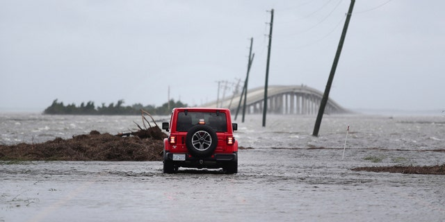 FILE - In this Friday, Sept. 6, 2019 file photo, storm surge from Hurricane Dorian blocks Cedar Island off from the mainland on NC 12 in Carteret County, N.C., after Hurricane Dorian passed the coast. A special United Nations-affiliated oceans and ice report released on Wednesday, Sept. 24, 2019 projects three feet of rising seas by the end of the century, much fewer fish, weakening ocean currents, even less snow and ice, and nastier hurricanes, caused by climate change. (AP Photo/Tom Copeland)
