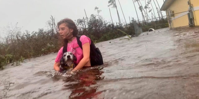 Julia Aylen breaks through deep waist water, carrying her pet dog while rescued from her flood home during Hurricane Dorian in Freeport, Bahamas, Tuesday, September 3, 2019.
