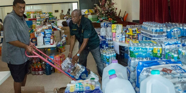 Ryan Smith, 60, left, and Hiram Williams, 71, stocking an auditorium with goods slated to be sent to the Bahamas at Christ Episcopal Church in Miami on Tuesday. (AP Photo/Ellis Rua)