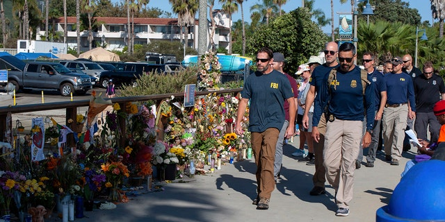 FBI agents walk past a memorial for the victims of the Conception dive boat on the Santa Barbara Harbor, as authorities issue a search warrant for the Truth Aquatics' offices in Santa Barbara, Calif., Sunday, Sept. 8, 2019.  (AP Photo/Christian Monterrosa)