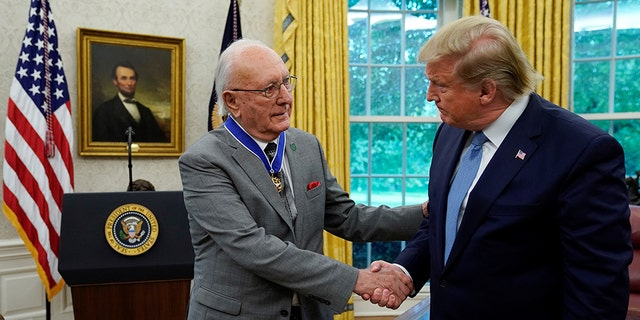 U.S. President Donald Trump greets Boston Celtics legend and Basketball Hall of Famer Bob Cousy prior to presenting Cousy with the Presidential Medal of Freedom to in the Oval Office of the White House in Washington, U.S., August 22, 2019. REUTERS/Kevin Lamarque - RC1A163A7F40