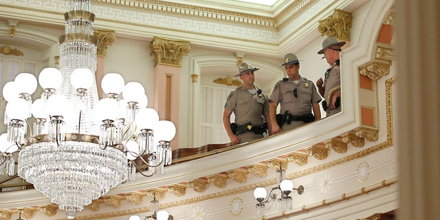 California Highway Patrol Officers inspect the Senate Gallery after a red substance was thrown from the gallery during the Senate session at the Capitol in Sacramento, Calif., Friday, Sept. 13, 2019. (AP Photo/Rich Pedroncelli)