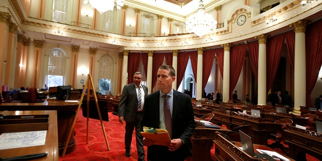 State Senator Mike McGuire, D-Healdsburg, right, leaves the Senate Chambers after a red substance was thrown from the Senate Gallery during the Senate session at the Capitol in Sacramento, Calif., Friday, Sept. 13, 2019. (AP Photo/Rich Pedroncelli)