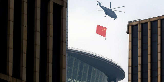 A helicopter carrying the Chinese flag flies above the central business district in Beijing on Sunday. (AP Photo/Mark Schiefelbein)