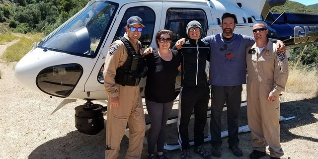 Krystal Ramirez, Hunter Whitson and Curtis Whitson, pictured with California Highway Patrol officials, were thankful to be rescued from an isolated tributary by sending an SOS message in a plastic Nalgene water bottle in June.