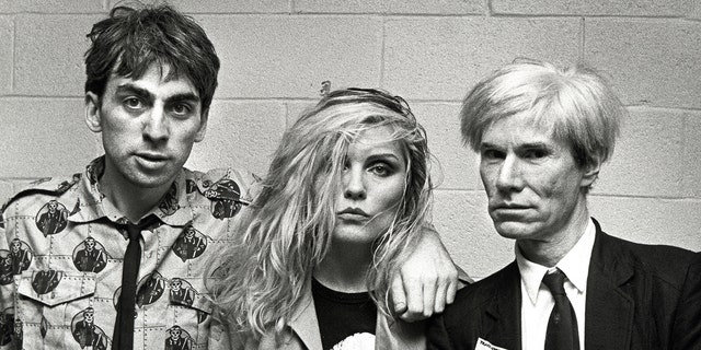 Chris Stein, Debbie Harry, and Andy Warhol pose ahead of a Blondie concert at the Meadowlands in New Jersey in August 1982.