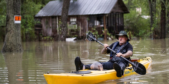 Donnie McCulley paddles out from a flooded neighborhood with an armadillo as a passenger. (Brett Coomer/Houston Chronicle via AP)