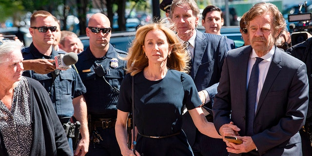Felicity Huffman, escorted by her husband William H. Macy, makes her way to the entrance of the John Joseph Moakley United States Courthouse Sept.13 in Boston.