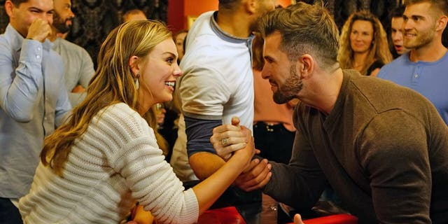 """The Bachelorette"" star Hannah Brown arm wrestles with contestant Jed Wyatt. Wyatt came under fire for allegedly having a girlfriend before leaving Nashville to film the reality series."