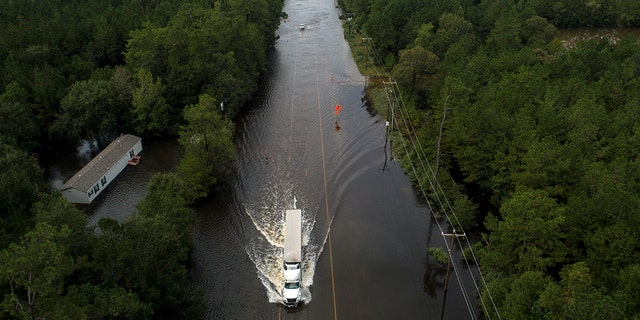 A truck drives through a flooded highway as flooding from the remnants of Tropical Storm Imelda continues in Southeast Texas on Friday, Sept. 20, 2019, in Mauriceville, Texas. (Jon Shapley/Houston Chronicle via AP)