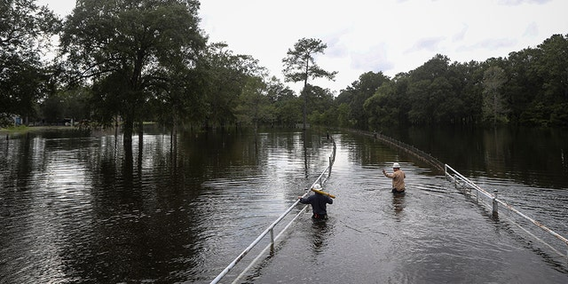 Mike Davis left and Trent Tipton both line workers from Woodville Texas walk through floodwater to try to restore power for a customer on Friday Sept. 20 2019 in the Mauriceville Texas area. Floodwaters are starting to recede in most of the Hous