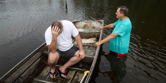 "Stephen Gilbert, left, and his father-in-law sit in front of their flooded property on Friday, Sept. 20, 2019, in the Mauriceville, Texas, area. Floodwaters are starting to recede in most of the Houston area after the remnants of Tropical Storm Imelda flooded parts of Texas. ""I'm on my third house,"" said Gilbert, who lives behind his father-in-law. ""I wouldn't go anywhere else in the world,"" he said. ""All we have is family anyway."" (Jon Shapley/Houston Chronicle via AP)"