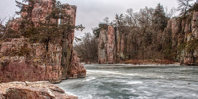 A woman survived falling down a cliff in South Dakota's Palisades State Park, officials said.
