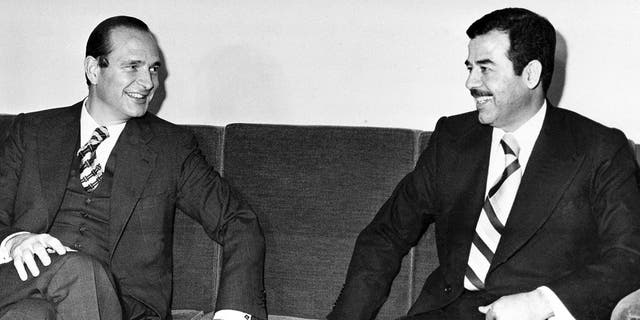 This file photo of then French Prime Minister Jacques Chirac, left, and Saddam Hussein of Iraq talk prior to a state dinner in Baghdad in 1974. (AP Photo/file)