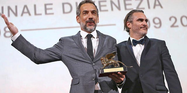 Director Todd Phillips, left, holds the Golden Lion for Best Film for