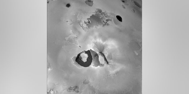 """This image from Voyager 1 shows the Loki volcano on Jupiter's moon Io. When this image was taken, the main eruption activity came from the lower left side of the dark linear feature (possibly a crack) in the middle. Below is the """"lava lake"""", a roughly 200 kilometers wide, U-shaped dark area. (Source: NASA / JPL)"""