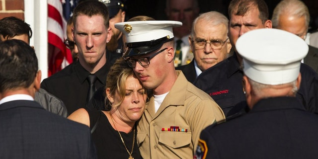 Erika Starke, left, is comforted by her son Michael Haub as they attend a second funeral service for New York Fire Department firefighter Michael Haub, in Franklin Square, N.Y., Tuesday, Sept. 10, 2019. (AP Photo/Eduardo Munoz Alvarez)