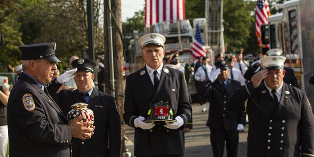 A New York Fire Department member, left, carries the remains of FDNY firefighter Michael Haub during second funeral service for him in Franklin Square, N.Y., Tuesday, Sept. 10, 2019. (AP Photo/Eduardo Munoz Alvarez)